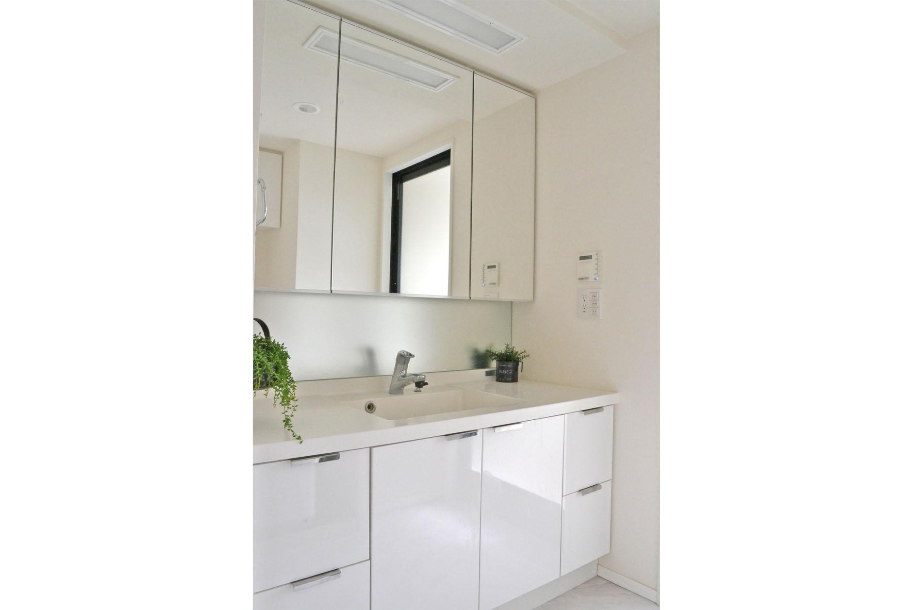 清潔感のある白を基調とした洗面台と高級感のある大理石調床タイル イメージ
