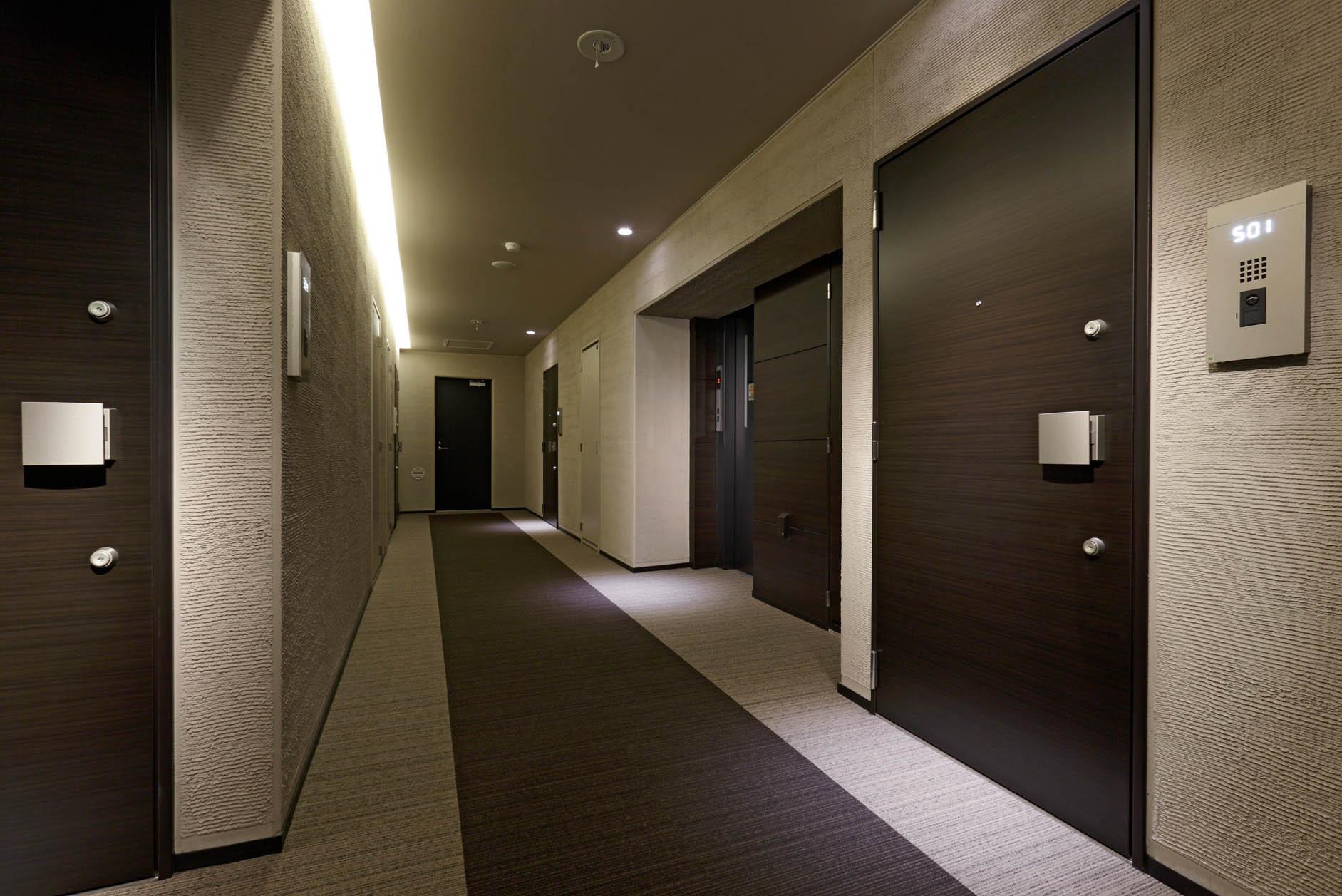 間接照明が印象的な、カーペット敷きの内廊下設計を採用しました。外部からの視線を遮り、各住戸の独立性を配慮した設計です。 イメージ