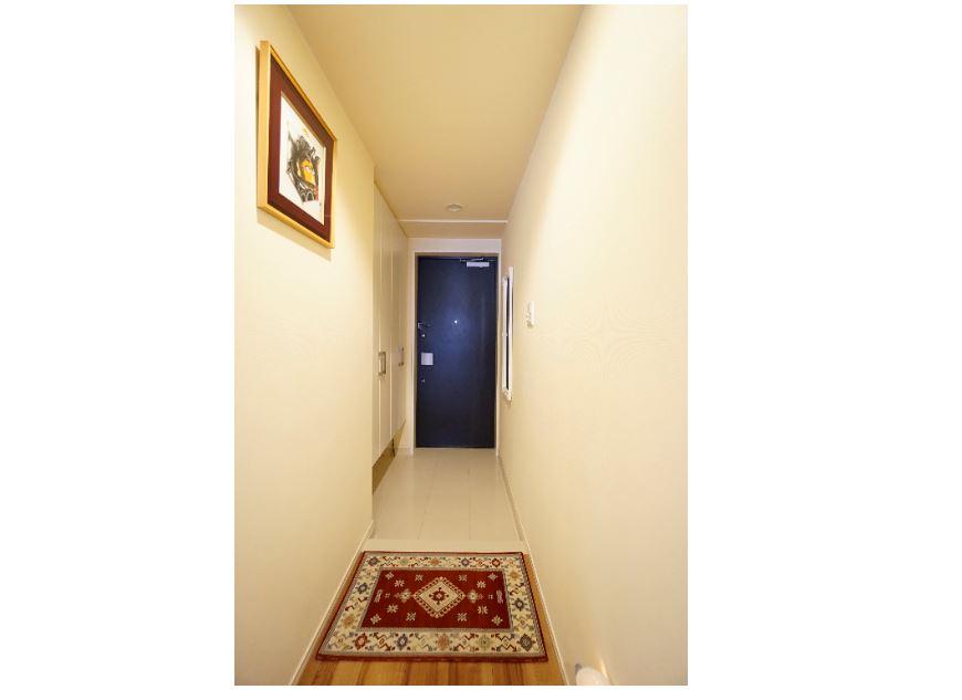 白色タイル貼りの玄関は人勧センサー付きのダウンライトと大型システム収納 イメージ