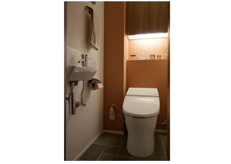 珪藻土の壁面と間接照明で照らされたタンクレストイレ&手洗い器 イメージ